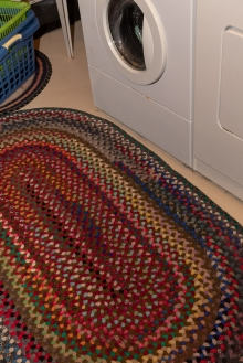 A lovely colored rug in front of the washer/dryer units.