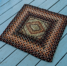 A hooked rug with braided edges. Fascinating colors.